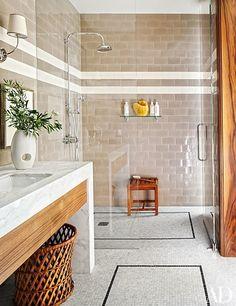 Shower fittings, shower shelf, teak stool, and mosaic-tile flooring, all by Waterworks   archdigest.com