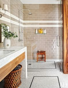 Shower fittings, shower shelf, teak stool, and mosaic-tile flooring, all by Waterworks | archdigest.com