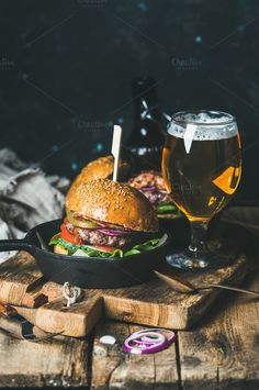 #Beef burgers with crispy bacon  Homemade beef burger with crispy bacon and vegetables in small pan and glass of wheat beer on rustic serving board over shabby wooden background dark blue plywood wall selective focus copy space