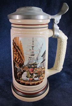 "1986 Shipbuilder Avon Beer Stein - This is a beautiful collectible beer stein that was produced by Avon in 1986. It features a woodworker in the foreground and a schooner in the background on one side and a wooden sign that reads shipbuilder and shows a picture of the schooner on the other. The handle has the appearance of being wrapped in a rope.  This item is in excellent condition and is approximately 9"" tall and weighs a little over two pounds."