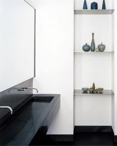 Slim white shelves in minimal black and white bathroom in a New York City loft by Deborah Berke  Partners Architects.