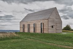 Summerhouse in Burgenland by Judith Benzer Architektur all made by long larch planks with large shutters that may be closed or folded open.
