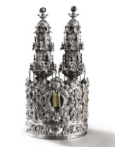 An important Italian silver torah crown & pair of torah finials, Venice -  The crown deeply embossed, chased & pierced with fruit, flowers & scrolled foliage enclosing applied emblems in recesses, including Priest's hat, Ark, Tablets of the Law, censer; the finials with staves chased with shells below spiralling foliage, hexagonal bodies applied with similar emblems...hung with pear-shaped bells, with later Hebrew inscription Nefesh Shalom Association in the year...1870/71.