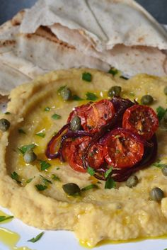 A delicious yellow split pea recipe from blogger Food Urchin, where the yellow split peas are transformed into a creamy dip, similar to the Greek fava dip, and served with roasted tomatoes and caramelised onions.