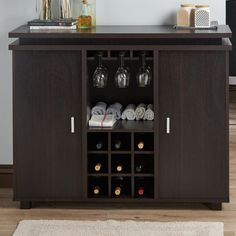 Be it an upscale cocktail party with friends or simply a well-deserved drink after work, a beautiful home bar is a must-have for the den. Start styling your mixologist-inspired space with this timeless server, then use its center storage to tuck away stemware and nine bottled reds, and finally adorn the top with liquor-filled decanters. Taking on a streamlined silhouette, this posh piece is crafted of manufactured wood with a rich espresso laminate finish. Take advantage of its two side…