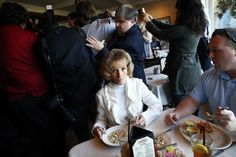 A woman eats clam chowder as media and supporters surround Republican presidential candidate Rick Santorum at a campaign event at a restaurant in Florence