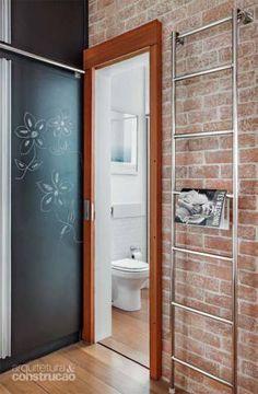 A porta de correr que dá acesso ao banheiro se esconde na lateral da despensa. Ao lado da abertura, a escada móvel de aço inox serve de revisteiro e facilita a alcançar a parte alta do armário. Projeto Escala Arquitetura e André Passini.