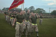 Lance Cpl. Adrian Simone, a rifleman with 1st Platoon, Company B, 1st Battalion, 6th Marine Regiment, throws up both hands to represent 1st Bn., 6th Marines at the end of the 2nd Marine Division run aboard Marine Corps Base Camp Lejeune, N.C., April 20. The Boonton, N.J., native lost both of his legs from the knee down after stepping on an improvised explosive device in Sangin, located in the southwest corner of Afghanistan.  2nd Marine Division  Photo by Cpl. Timothy Solano