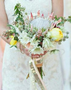 Lovely Bridal Bouquet: Pink King Protea, Blushing Bride Protea, White Scabiosa Flowers, Yellow Tulips, Yellow Cabbage Roses, Other Coordinating Florals & Foliage Hand Tied With Pink & Sequined Ribbons