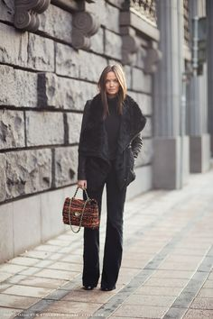 "Columbine Smille in a shearling coat, black turtleneck and trousers, and MULBERRY ""Lily"" boucle wool tweed shoulder bag."