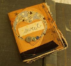 this fabric book looks more like a journal to me then a photo keepsake book.. would be very cute to have my journals wrapped in fabric! {oh and don't leave out the buttons!}