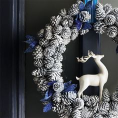 pinecones painted white with blue ribbon and white deer...