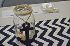 Center pieces made from Mason Jars with twine rope hot glued around and painted anchors.  Complete with sand in jar, shells, and a battery operated tea light.