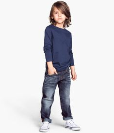 Blue sweatshirt, jeans, and white canvas shoes