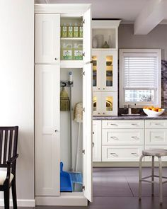 A tall narrow cupboard hides all the paraphernalia for cleaning as well as the bulk buy items