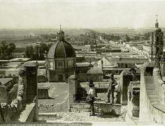 Imagen de la vista trasera de la Basilica de Guadalupe, al fondo la Calzada de Guadalupe y mas a la derecha la Calzada de los Misterios, Al fondo la Ciudad de Mexico. La imagen fue tomada desde las escalinatas que conducen al Templo en el cerro del Tepeyac. ca. 1883