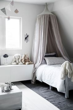 Simple and muted child's bedroom with a hint of floral vintage in the pillowcase. A place for little girls to read and create their own dreams