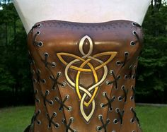 Ladies Corset made of genuine, vegetable tanned leather.  Carved, tooled, molded and laced by hand.  Hand painted and dyed using ecofriendly leather dye to ensure water resistance and color fastness. Finished with a beeswax top coat.  You can also contact us to custom order your own corset. You can choose a different color pattern and/or design. While the product is new, it can be firm, but will get softer with wear. This 13 panel corset is designed to fit most cup sizes and body types....