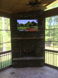 Outdoor fireplace in screen porch with TV and EZE Breeze Windows by Archadeck