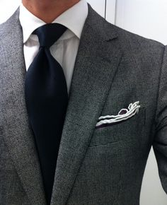 Navy tie, gray blazer, white shirt, pocket square.