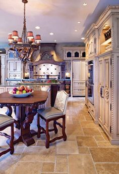 French Country Elegance.  Gorgeous French Country kitchen, off white cabinets, blue grey accents, beautiful wood sitting area, limestone floors, elegant country chandelier.