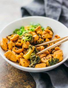 Using chopsticks to eat Asian cashew chicken and broccoli in a bowl