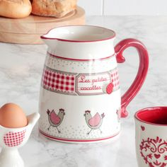 A delightful jug perfect for serving fruit juices or fresh milk. Featuring a hen design and a sturdy red handle, this would be an ideal addition to the breakfast table.  Made from ceramic with a high shine and off white finish, complete with a red rim to the top, the jug depicts running hens to the base and a checker banner with the wording 'Les petites Cocottes' translating to 'The Small Pots'.  The generous sized jug can hold up to a litre of your favourite juice or milk.