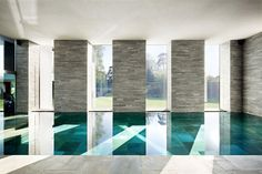 The Suffolk Poolhouse by David Mikhail Architects, pool room with four 5m high, bespoke sliding glass doors _