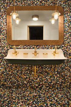 Charming colorful cottage boy's bathroom is clad in colorful hexagon floor and wall tiles and boasts a black trough sink fitted with three brass gooseneck faucets lit by nautical pendant lights hung in front of a curved woven vanity mirror. Mirror With Lights, Hanging Lights, Home Developers, Bali Decor, Trough Sink, Bathroom Kids, Bathrooms, Sink Design, Vanity Sink
