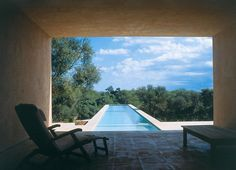 Located in Mallorca Spain Neuendorf House (1991) by John Pawson  Claudio Silvestrin. This vacation house for a German art dealer is set in an almond grove on the island of Mallorca with views of sea and mountains. The composition of the atrium is emphatically vertical the exaggerated height of the walls dramatized by the narrowness of the slot opening. #johnpawson #pawson #spain #spanish #composition #details #pool #swimming #swimmingpool #view #shadows