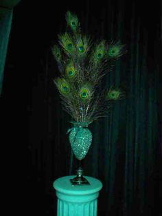 Peacock Wedding Ideas, Peacock Wedding Supplies  This is my tall centerpiece, went to the dollar store to recreate more cost effectively here is the breakdown   Vase $1 Candleholder (to add height) $1  Accent Gems (4 bags) $4 Led Lights $1 Peacock feathers (10) $5 Ribbon $1.50  Grand total $13.50