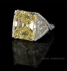 Fancy Yellow Diamond flanked by two trillion Diamonds.