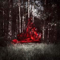 red riding hood  a conceptual fine art portrait set in the woods. it depicts a girl in a red cloak and is a dark twist on the classic fairy tale of little red riding hood