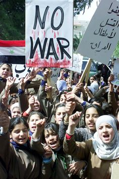 """April 2, 2003 - Some 1,500 Syrian school children stage a sit in outside the UNICEF offices in Damascus to protest the US-British war on Iraq. They carried banners, one of them reading """"Stop killing Iraqi children."""" (AP Photo Bassem Tellawi)"""