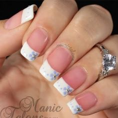 This french manicure gets soft lavender floral accents and metallic studs to embellish the regular nude and white nail polish. Try this nail art design with this how-to guide.
