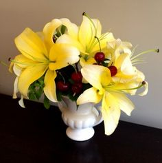 I used cherries to dress up a few stems of butter yellow Conca D'or lilies that I placed in a classic white urn. Simple, yet unexpected, this arrangement is sure to make people smile as they walk by. // sarah von pollaro