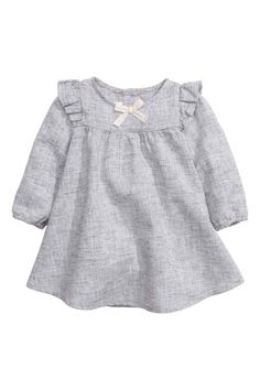Dress in a linen blend: BABY EXCLUSIVE. Dress in a marled linen and cotton weave with frills at the shoulders, a decorative bow at the front, button at the back of the neck and long sleeves with elasticated cuffs.