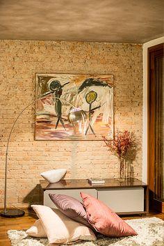 Detalhe de sala de estar com piso de madeira, parede de tijolos originais descascados, cimento queimado no teto, tapete e almofadas do chão