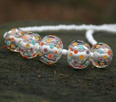 This looks like clear beads with white dotes and these dots are stacked with bright opaque colors!