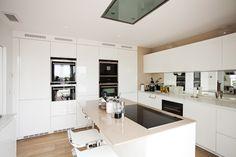 #Cocina en blanco con pared y #encimera isla en color moka. #Isla central en #compact (Silestone) #Mueble auxiliar de #Corian. Grupo filtrante integrado en techo.Columnas con horno, microondas, cafetera.