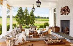 A side porch features brass lanterns from Circa Lighting and Munder-Skiles furniture with Perennials-fabric cushions.