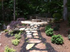 Flagstone walkway to a stone patio with firepit.