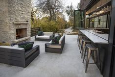 Outdoor, Back Yard, Large Patio, Porch, Deck, Trees, Wood Fences, Wall, Shrubs, Walkways, Concrete Patio, Porch, Deck, and Horizontal Fences, Wall The kitchen bar counter extends out to the patio, creating a great space for entertaining. Photo 9 of 12 in A Colorado Home Puts a Modern Twist on Farmhouse Living