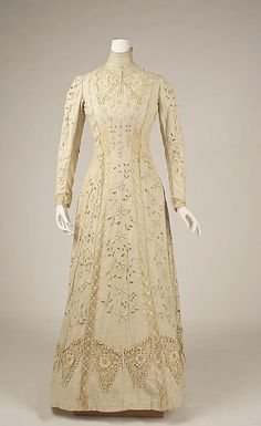 Edwardian Ivory linen day dress. (circa 1910) This shows the gown without it's matching overcoat. Here the cutwork and heavy lace appliques are easily visible. The dress has a high-throat collar and long narrow sleeves.