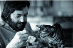 Julio Cortazar feeding his tabby cat
