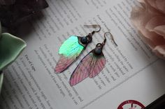 Beautiful iridescent fairy wing earrings that have been electroformed with rainbow moonstone cabochons. This pair have a colour combination of pink and green! The wings were created by Mad March Moon…