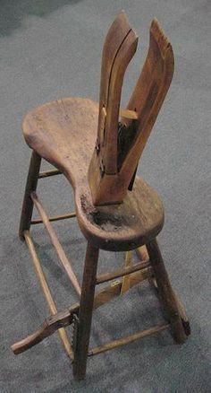 The four sawhorse looking things in the front row are harness makers' vises (also known as saddle maker's vises when used for that purpose). The harness maker presses his right foot down on the lever and the jaws clamp the piece of leather, freeing up both hands so that he can sew or trim. Here's an older one: