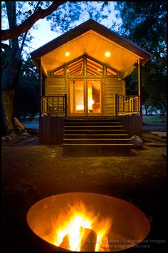 Evening campfire in fire pit in front of rustic wood cabin, El Capitan Canyon Resort, near Santa Barbara, California - ID# SBAR-2074