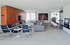 Os ambientes do living são unidos por elementos horizontais: a bancada de mármore preto e a caixa de madeira pau-ferro, que embute a TV e o duto da lareira, apoiada na laje em balanço (esq.). O piso, cinza, é completamente neutro. Projeto do escritório Zemel   Chalabi