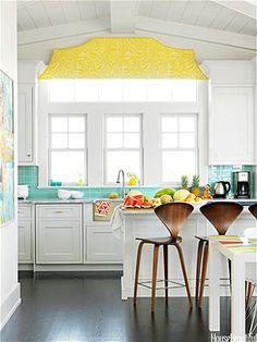 """Pops of color  """"The kitchen has a classic, timeless quality,"""" designer Mona Ross Berman says of a home in Strathmere, New Jersey. """"With a few fun pops of color to keep it from being staid and predictable""""—like the fanciful valance in Arcadia Sulphur by Raoul Textiles and the Modwalls glass tile backsplash."""
